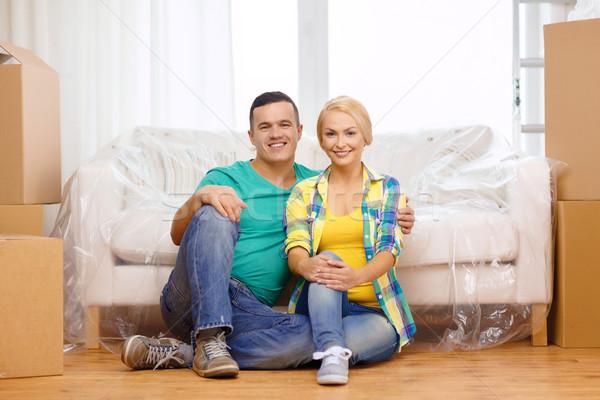 Uśmiechnięty para posiedzenia piętrze ruchu Zdjęcia stock © dolgachov