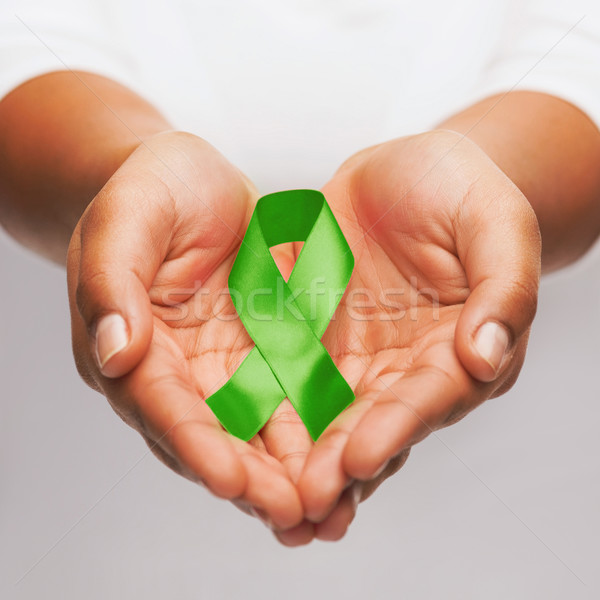 hands holding green awareness ribbon Stock photo © dolgachov