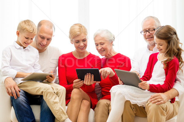 Stock photo: smiling family with tablet pc computers at home