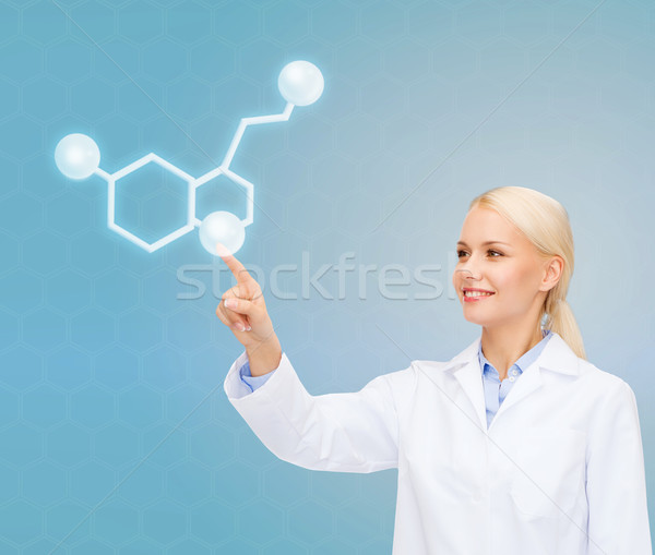 smiling female doctor pointing to molecule Stock photo © dolgachov