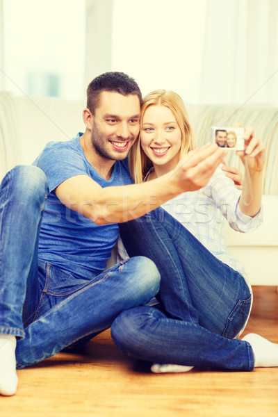 smiling couple taking picture with digital camera Stock photo © dolgachov