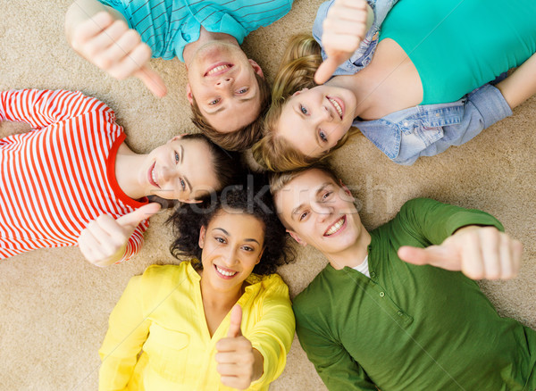 Stock photo: group of smiling people lying down on floor