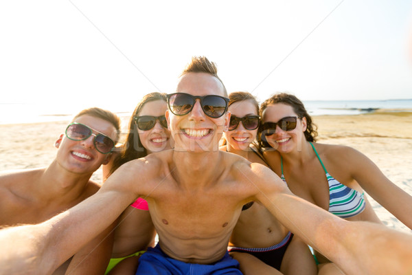 Stock photo: group of smiling friends making selfie on beach