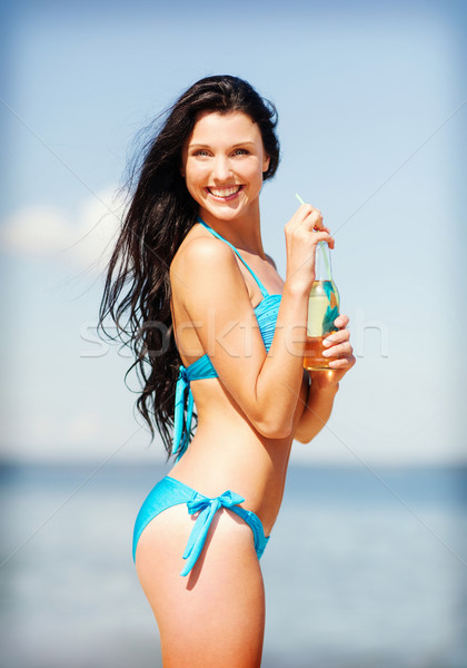 girl with bottle of drink on the beach Stock photo © dolgachov