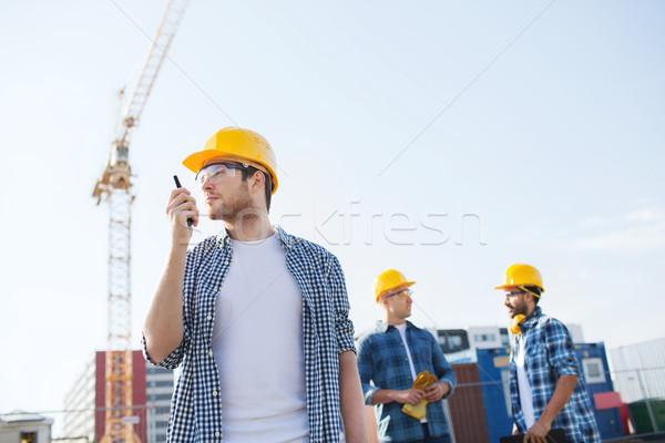 group of builders in hardhats with radio Stock photo © dolgachov