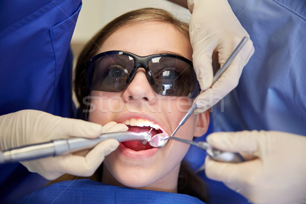female dentists treating patient girl teeth Stock photo © dolgachov