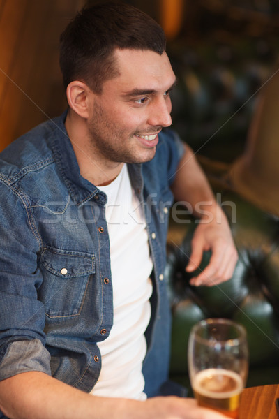 happy man drinking beer at bar or pub Stock photo © dolgachov