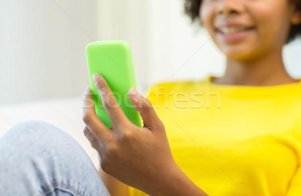 Felice african donna smartphone home persone Foto d'archivio © dolgachov