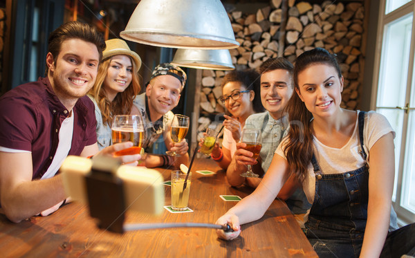 friends with smartphone on selfie stick at bar Stock photo © dolgachov