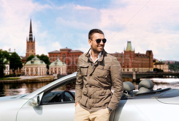 man near cabriolet car over city of stockholm Stock photo © dolgachov