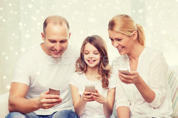 happy family with smartphones at home Stock photo © dolgachov