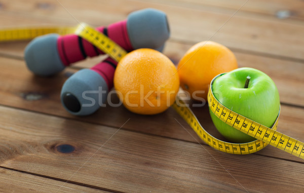 Stock photo: close up of dumbbell, fruits and measuring tape