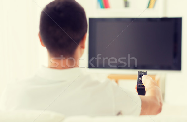 Stock photo: man watching tv and changing channels at home