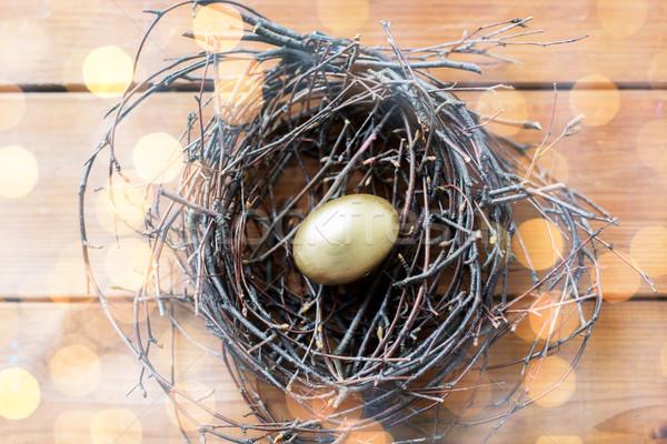 close up of golden easter egg in nest on wood Stock photo © dolgachov