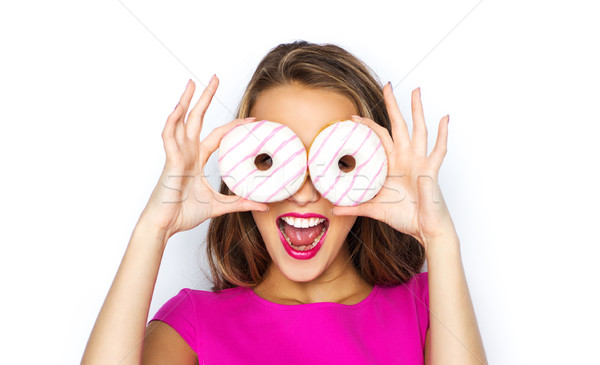 Stock photo: happy woman or teen girl looking through donuts