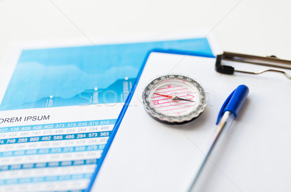close up of compass on financial report document Stock photo © dolgachov