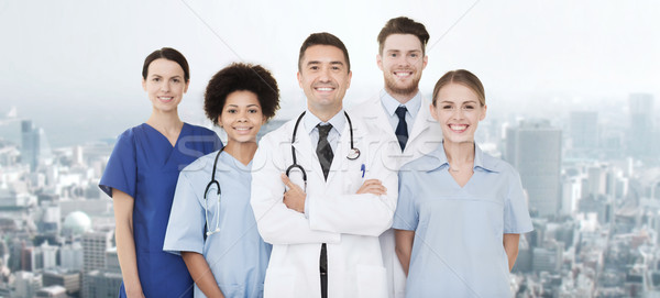 group of happy doctors over blue background Stock photo © dolgachov