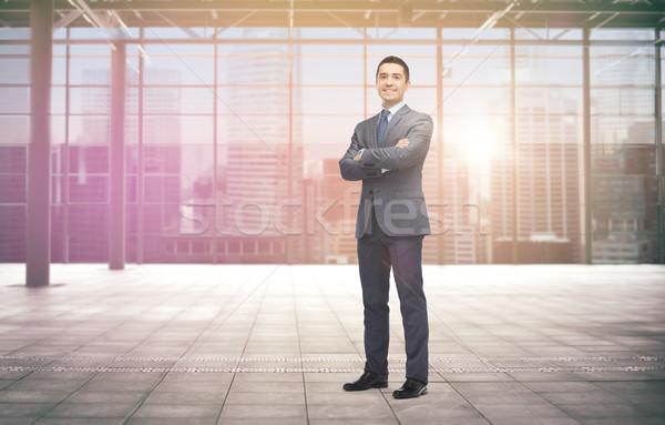 smiling businessman over empty hall and city Stock photo © dolgachov