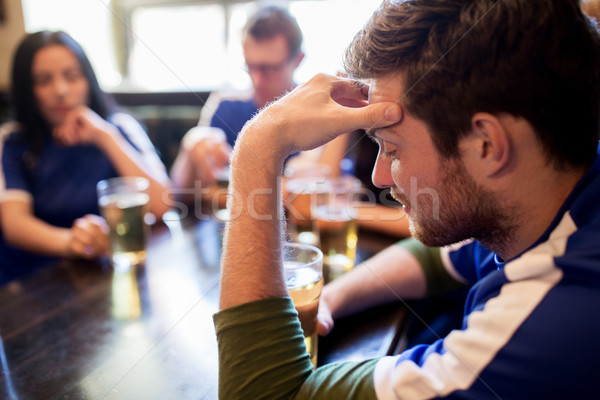 soccer fans watching football match at bar or pub Stock photo © dolgachov