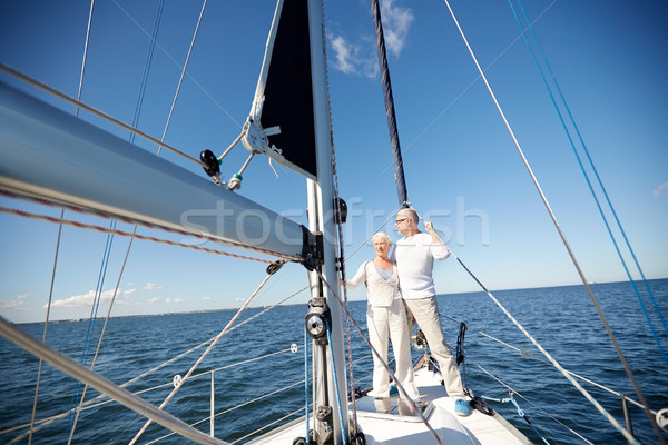 senior couple hugging on sail boat or yacht in sea stock