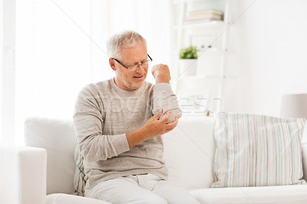 unhappy senior man suffering elbow pain at home Stock photo © dolgachov