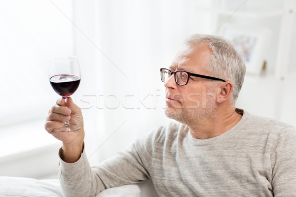 senior man drinking red wine from glass at home Stock photo © dolgachov