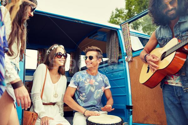 happy hippie friends playing music over minivan Stock photo © dolgachov