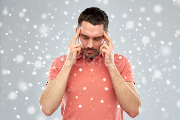 man suffering from head ache or thinking over snow Stock photo © dolgachov