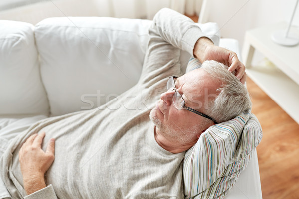Stock photo: close up of senior man in glasses thinking at home
