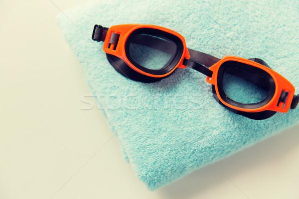 close up of swimming goggles and towel Stock photo © dolgachov