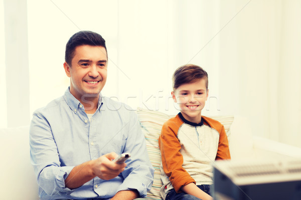 smiling father and son watching tv at home Stock photo © dolgachov