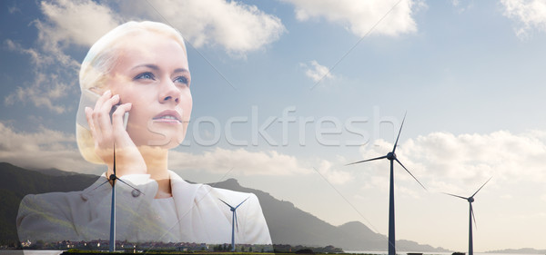 businesswoman with smartphone over wind turbines Stock photo © dolgachov
