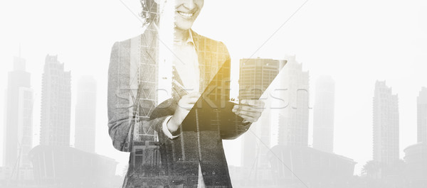 businesswoman with clipboard over city buildings Stock photo © dolgachov