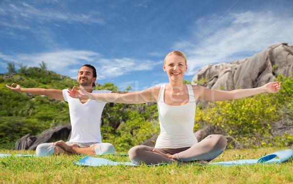 happy couple making yoga exercises outdoors Stock photo © dolgachov