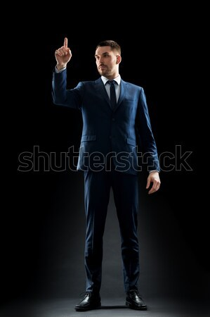 businessman in suit holding something invisible Stock photo © dolgachov
