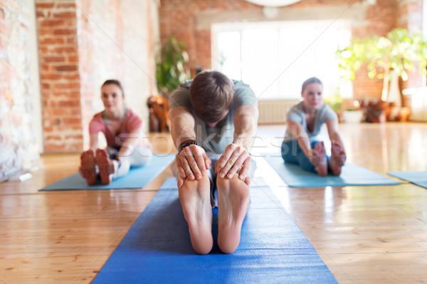 group of people doing yoga forward bend at studio Stock photo © dolgachov