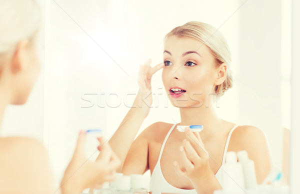 young woman putting on contact lenses at bathroom Stock photo © dolgachov