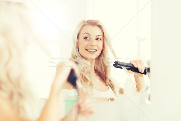 woman with styling iron doing her hair at bathroom Stock photo © dolgachov