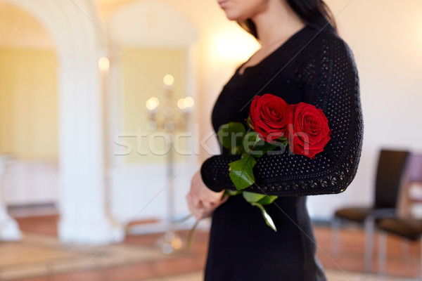 woman with red roses at funeral in church Stock photo © dolgachov