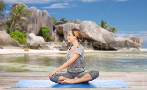 woman doing yoga in twist pose on beach Stock photo © dolgachov