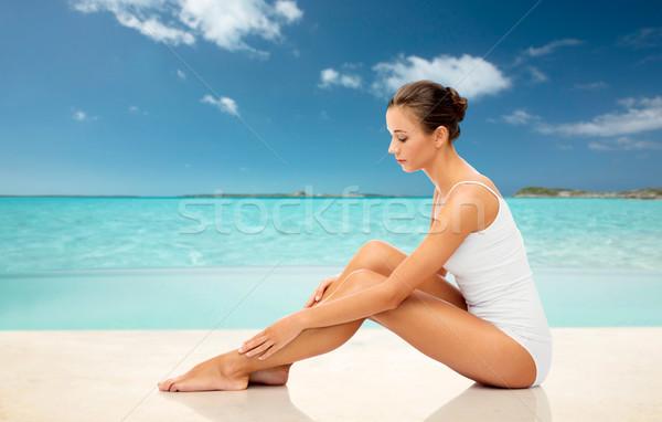 beautiful woman touching her smooth legs on beach Stock photo © dolgachov