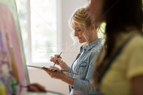 woman artist with palette painting at art school Stock photo © dolgachov