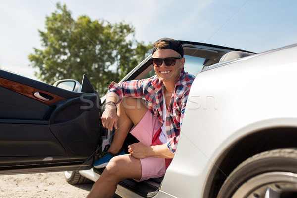 happy young man sitting in convertible car Stock photo © dolgachov