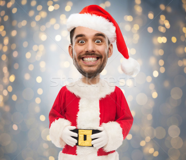 man in santa claus costume over christmas lights Stock photo © dolgachov