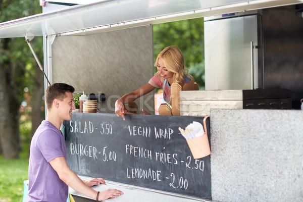 saleswoman at food truck serving male customer Stock photo © dolgachov