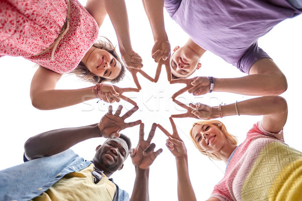 group of happy friends showing peace hand sign  Stock photo © dolgachov