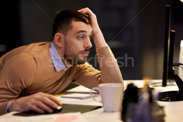 tired man on table at night office Stock photo © dolgachov