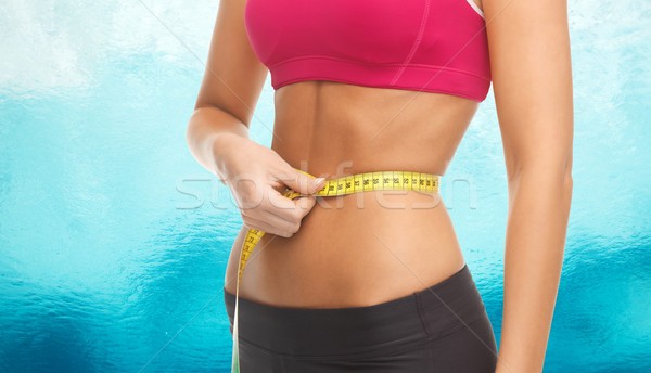 close up trained belly with measuring tape Stock photo © dolgachov