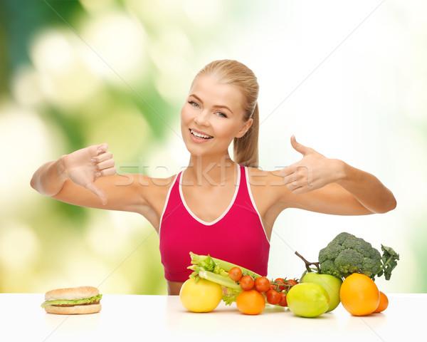 woman with fruits and hamburger comparing food Stock photo © dolgachov