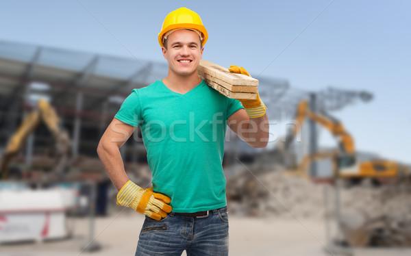 Sorridente manual trabalhador capacete edifício Foto stock © dolgachov